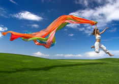 photo shows woman leaping whilst holding flowing coloured streamers out behind her - to give the impression of moving forwards through re training after being made redundant